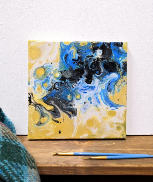 Acrylic Pouring Bild mit Blau und Gelb es liegen Pinsel im Vordergrund